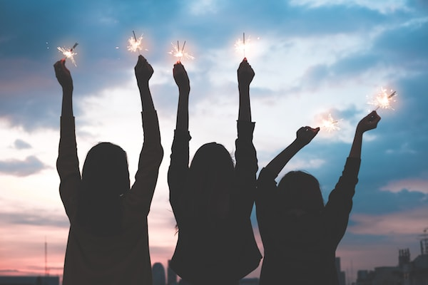 three women holding sparklers in the air at dusk