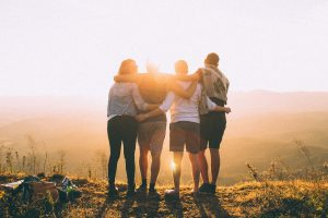 four people arm in arm at dawn in sunlight