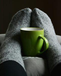 grey sock feet around green coffee mug on pillow